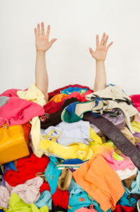 Hands sticking up out of a pile of clothing